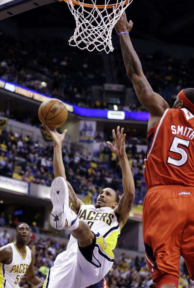 Pacers guard George Hill, who had 22 points, falls back while being fouled under Atlanta forward Josh Smith in Game 2 in Indianapolis. Photo: Michael Conroy / Associated Press