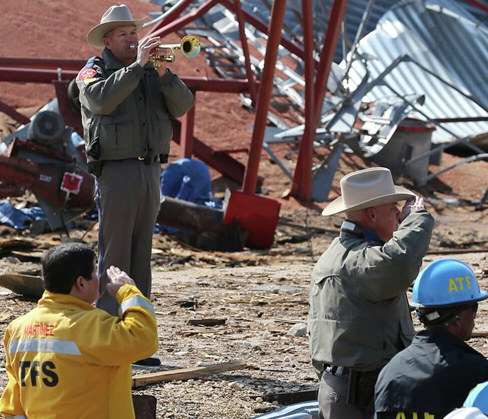 An officer sounds taps at a memorial ceremony at the site of the fire and explosion in West, Texas on April 24 2013.