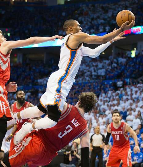Thunder point guard Russell Westbrook drives over Rockets center Omer Asik (3), who was called for a