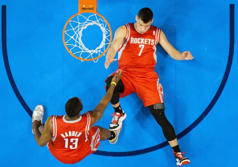 Rockets point guard Jeremy Lin (7) gets a hand from James Harden (13) as he gets up from the floor a