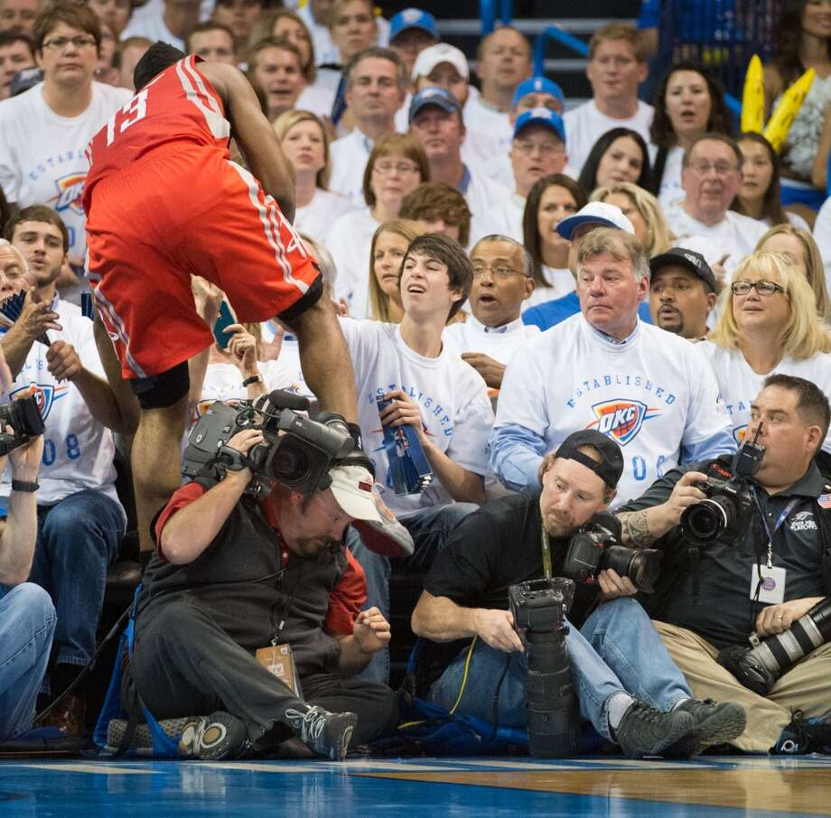 Rockets guard James Harden tumbles into the crowd chasing a loose ball. Photo: Smiley N. Pool, Houston Chronicle