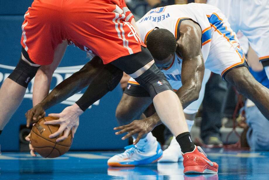 Thunder center Kendrick Perkins fights for a loose ball against Rockets center Omer Asik . Photo: Smiley N. Pool, Houston Chronicle