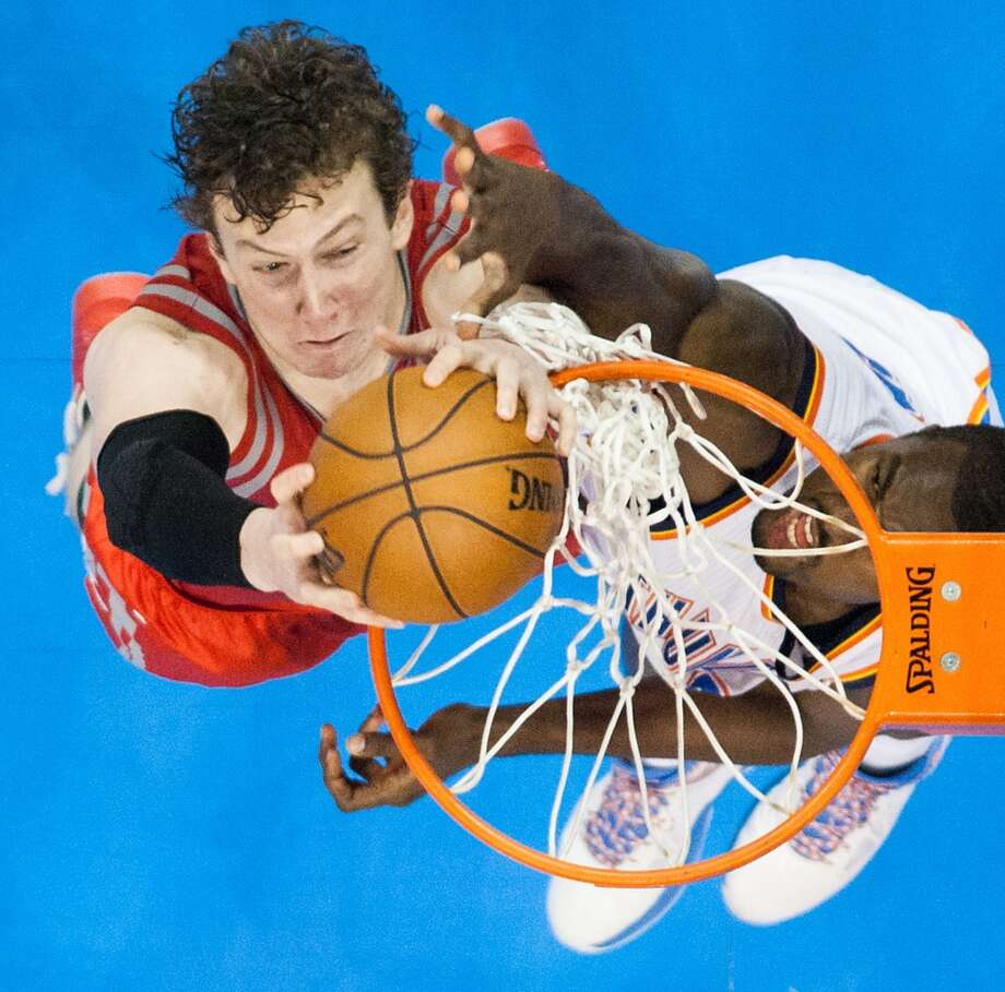 Rockets center Omer Asik dunks the ball past Thunder power forward Serge Ibaka during the second half. Photo: Smiley N. Pool, Houston Chronicle