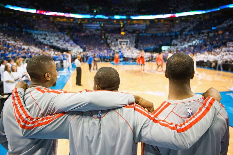 Rockets reserves stand arm-in-arm for the opening tipoff of Game 2.