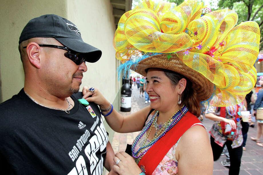 Dolores Ruiz pins her husband as NIOSA begins its's 2013 run at La Villita on  April 23 2013. Photo: TOM REEL