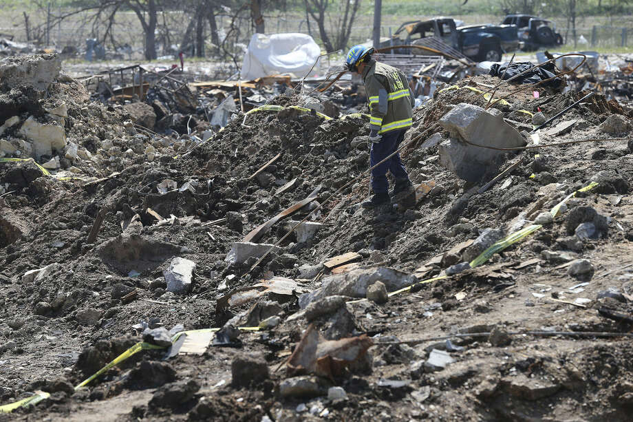 An ATF investigator descends into the crater — 93 feet wide and 10 feet deep — at the site of the April 17 explosion in West. Photo: Photos By Tom Reel / San Antonio Express-News