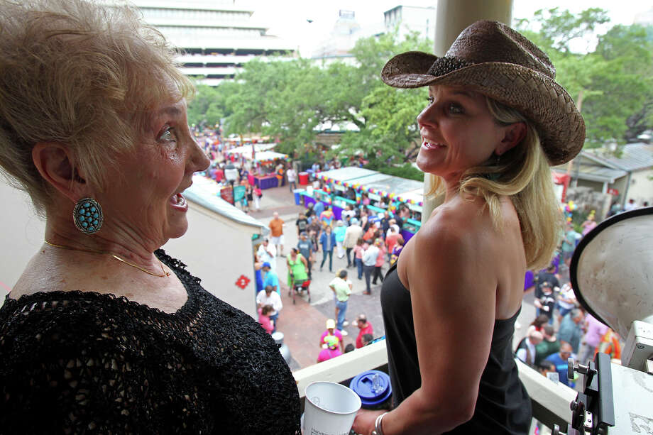 Sam Grandy (left) chats with Jeni Morrison as they watch the crowds from an elevated view as NIOSA begins its's 2013 run at La Villita on  April 23 2013. Photo: For The San Antonio Express-News