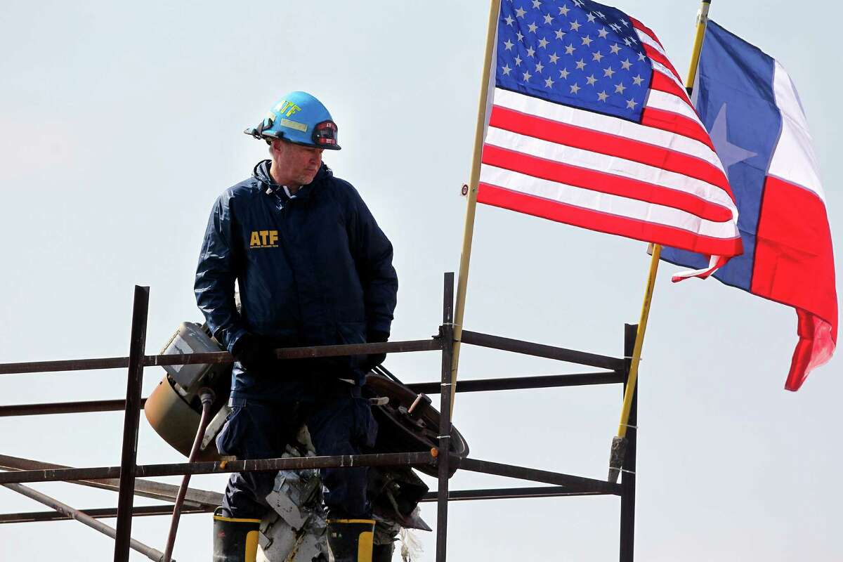 An ATF agent unveils flags for during a memorial ceremony at the site of the fire and explosion in West, Texas on April 24 2013.