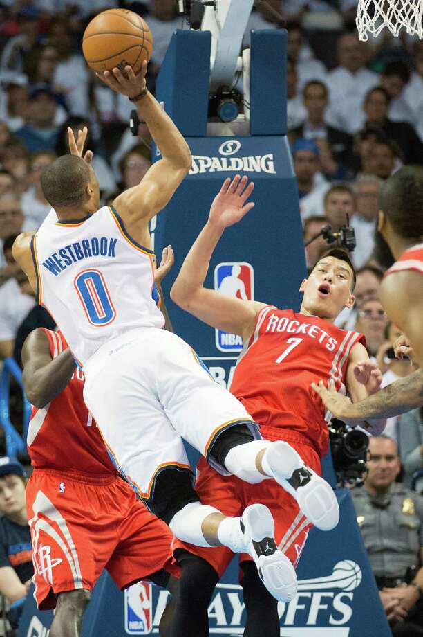 Although Jeremy Lin, right, wins the battle by drawing a charge on a first-half drive by Thunder guard Russell Westbrook, the Rockets point guard may have lost the war since he didn't play in the second half Wednesday because of a bruised chest muscle. Photo: Smiley N. Pool, Staff / © 2013  Houston Chronicle