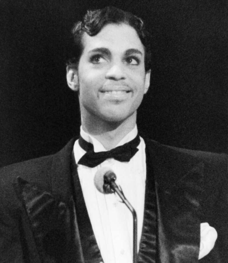 """Singing star Prince is all smiles as he addresses the audience at the American Music Awards, Jan. 27, 1986 in Los Angeles. He was up for several awards but did not place, but did present the award in the Pop-Rock Category for favorite single to Huey Lewis for his \""""Power of Love,\"""" hit. (AP Photo/Nick Ut)"""