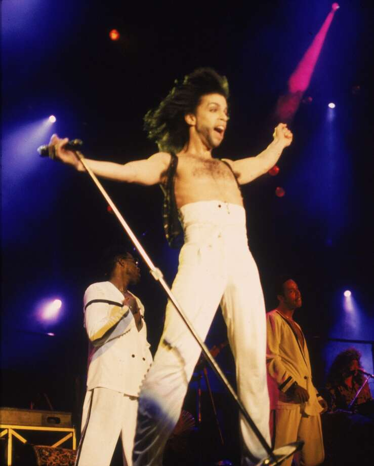 American singer and songwriter Prince stands on stage with his arms outstretched, wearing high-waisted white pants, circa 1990. (Photo by Frank Micelotta/Getty Images)