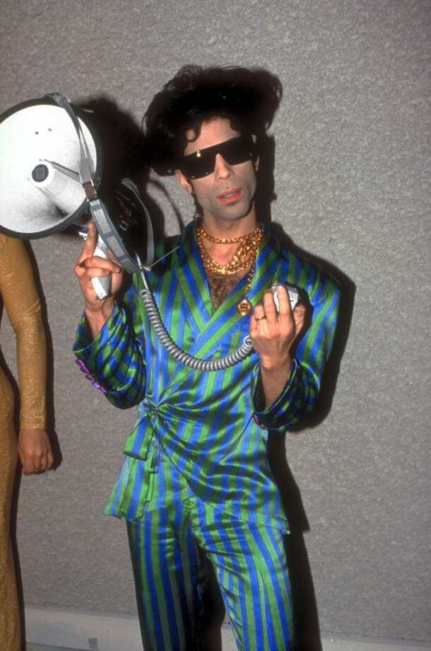Singer Prince wearing custom-made purple & green striped pajamas & holding bullhorn.  (Photo by Ron Wolfson//Time Life Pictures/Getty Images)