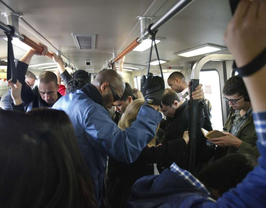 Passengers on crowded BART train hold onto hand straps as they travel through Oakland.