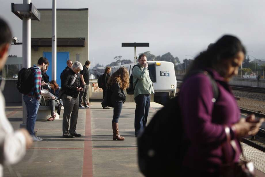 BART passengers wait on the station platform as they prepare to board a train as it arrives in the morning.