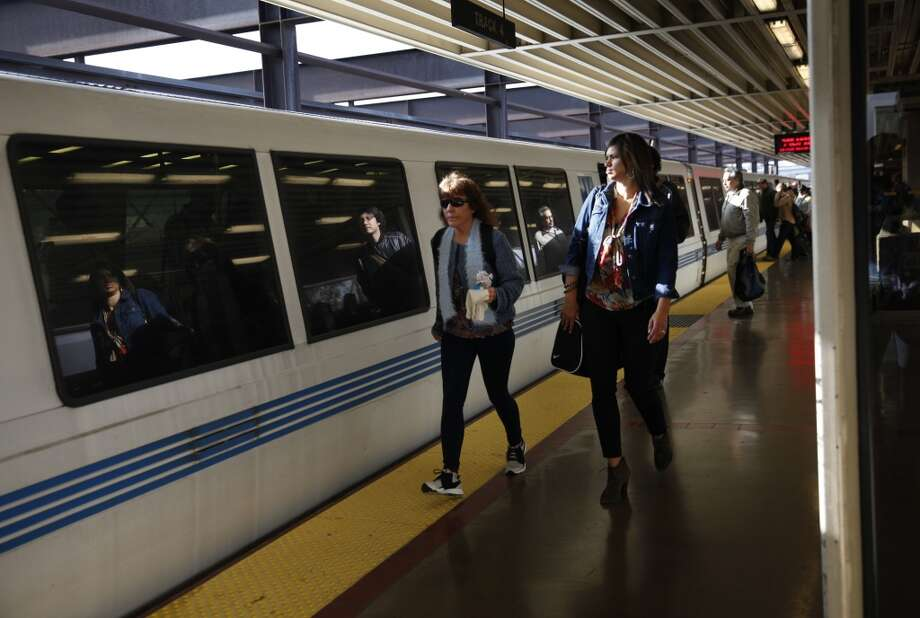 BART passengers make their way on the station platform as they prepare to board a train in the morning.