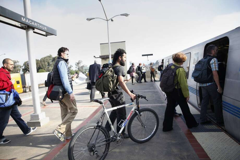 Jason Pichardo of Oakland holds onto his bike as he and other BART passengers on the station platform prepare to board a train.