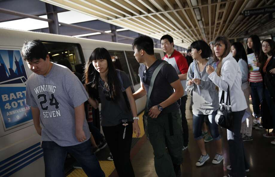 A group of BART passengers move to another train as the one they were standing at becomes crowded while boarding a train.