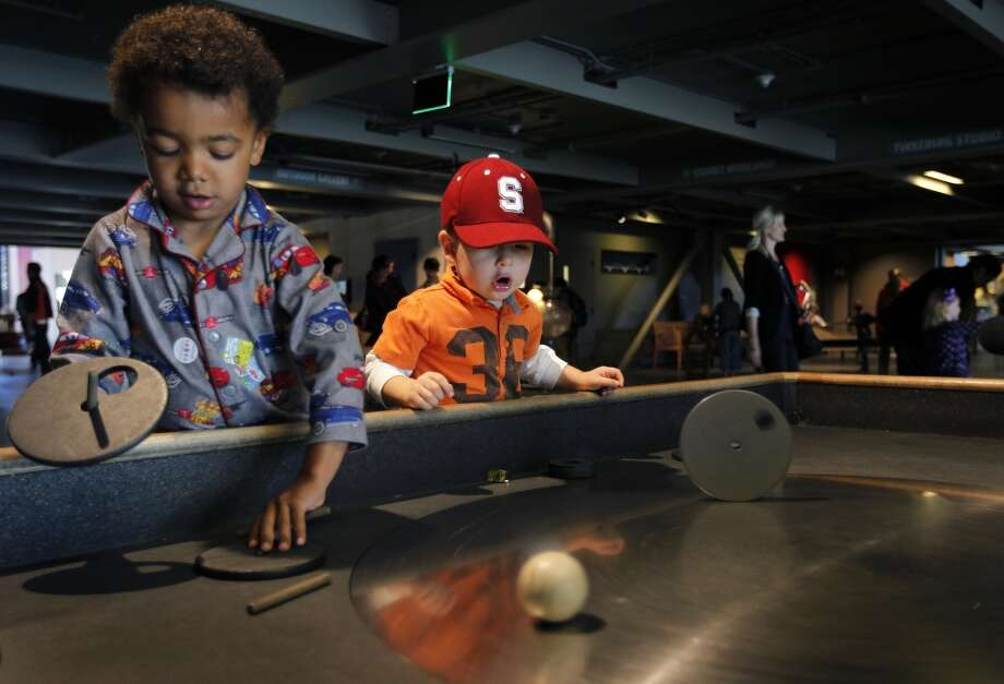 April 17, 2013: Axel Palms (left), 3, and Aiden Lombardo, 2, spin objects on a steel turntable on the opening day of the new Exploratorium science museum at Pier 15.