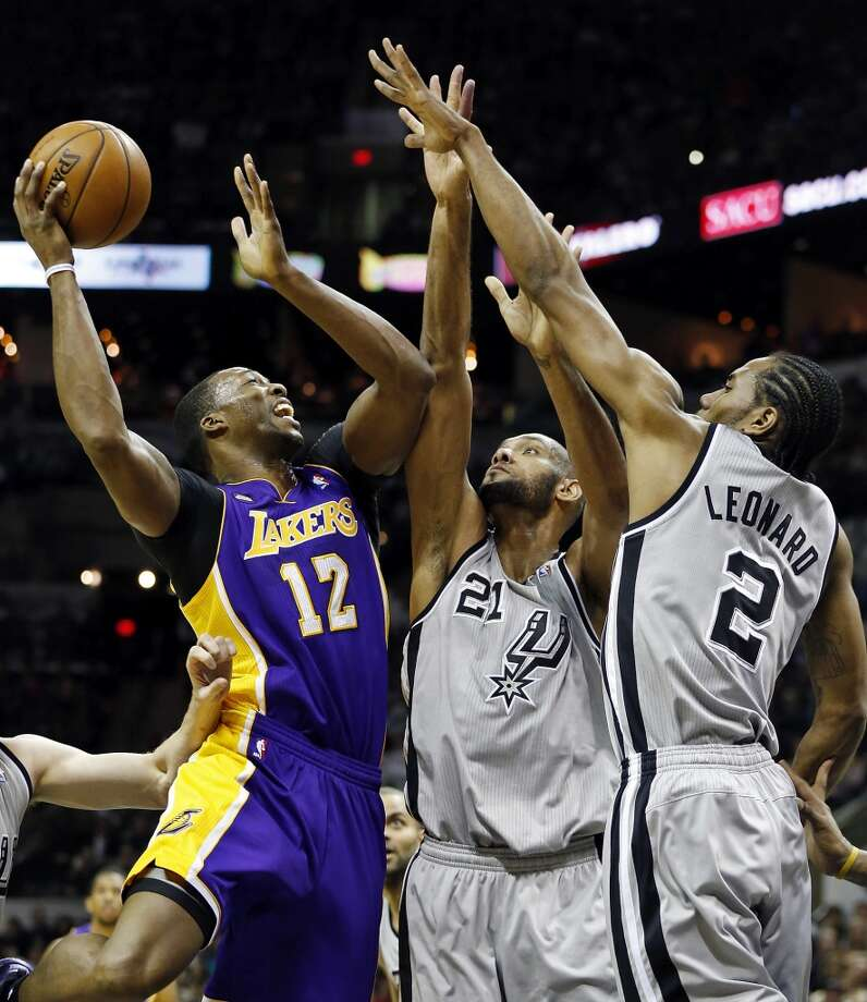 Los Angeles Lakers' Dwight Howard is defended by San Antonio Spurs' Tim Duncan and San Antonio Spurs' Kawhi Leonard during first half action of game 2 in the first round of the NBA Playoffs Wednesday April 24, 2013 at the AT&T Center.