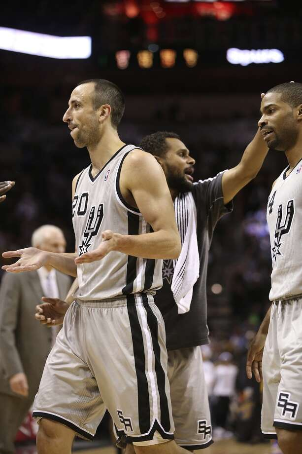 San Antonio Spurs' Manu Ginobili and Danny Green walks off the court and are greeted by Patty Mills as they lead in the second half of game 2 in the first round of the NBA Playoff against the Los Angeles Lakers at the AT&T Center, Wednesday, April 24, 2013. The Spurs won102-91 and lead the series 2-0.