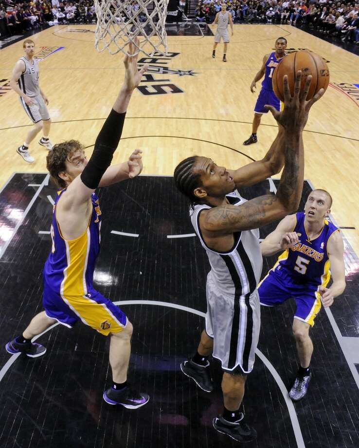 San Antonio Spurs' Kawhi Leonard shoots between Los Angeles Lakers' Pau Gasol (left) and Los Angeles Lakers' Steve Blake during first half action of game 2 in the first round of the NBA Playoffs Wednesday April 24, 2013 at the AT&T Center. The Spurs won 102-91.