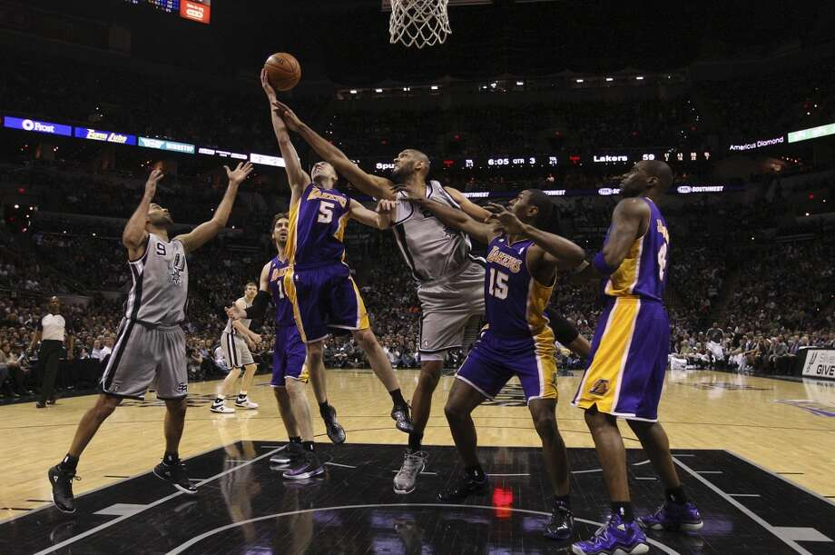 San Antonio Spurs' Tim Duncan goes for a rebound against Los Angeles Lakers' Steve Blake, (5), and Metta World Peace, (15), in the second half of game 2 in the first round of the NBA Playoff at the AT&T Center, Wednesday, April 24, 2013. The Spurs won102-91 and lead the series 2-0.