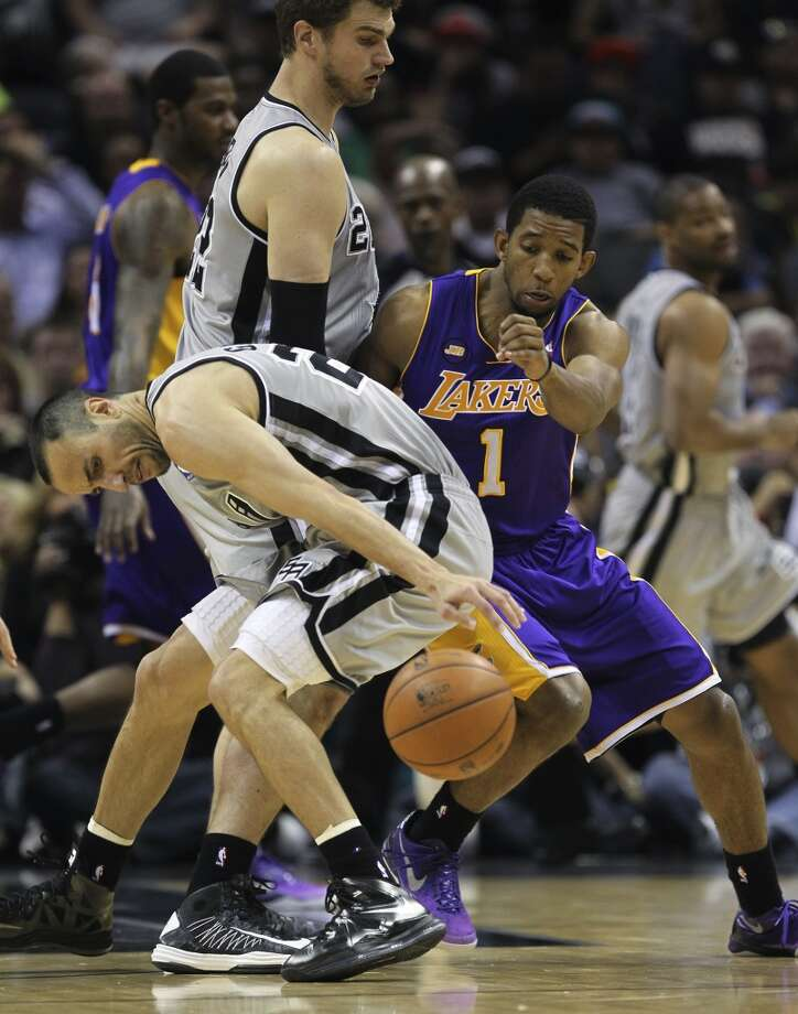 San Antonio Spurs' Manu Ginobili loses the ball as Tiago Splitter keeps Los Angeles Lakers' Darius Morris away in the second half of game 2 in the first round of the NBA Playoff at the AT&T Center, Wednesday, April 24, 2013. The Spurs won102-91 and lead the series 2-0.