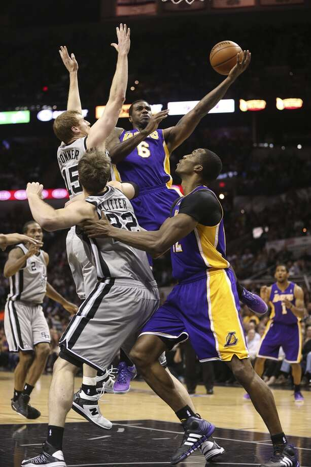 Los Angeles Lakers' Earl Clark goes over San Antonio Spurs' Matt Bonner and Tiago Splitter as Dwight Howard helps out in the second half of game 2 in the first round of the NBA Playoff at the AT&T Center, Wednesday, April 24, 2013. The Spurs won102-91 and lead the series 2-0.