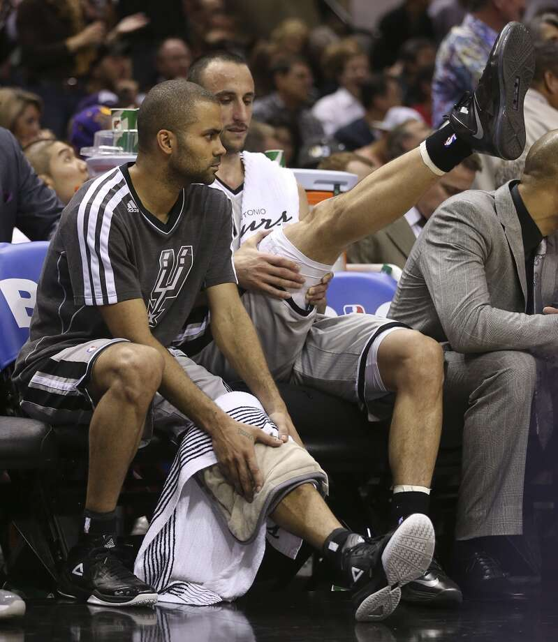 San Antonio Spurs' Tony Parker applies heat to his leg as Manu Ginobili stretches while sitting in the bench in the second half of game 2 in the first round of the NBA Playoff against the Los Angeles Lakers at the AT&T Center, Wednesday, April 24, 2013. The Spurs won102-91 and lead the series 2-0.