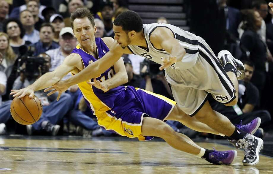 Los Angeles Lakers' Steve Nash and San Antonio Spurs' Cory Joseph chase after a loose ball during second half action of game 2 in the first round of the NBA Playoffs Wednesday April 24, 2013 at the AT&T Center. The Spurs won 102-91.