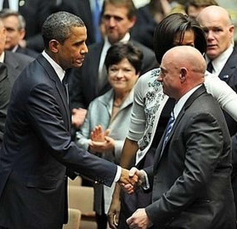 The president greets retired NASA astronaut Mark Kelly.