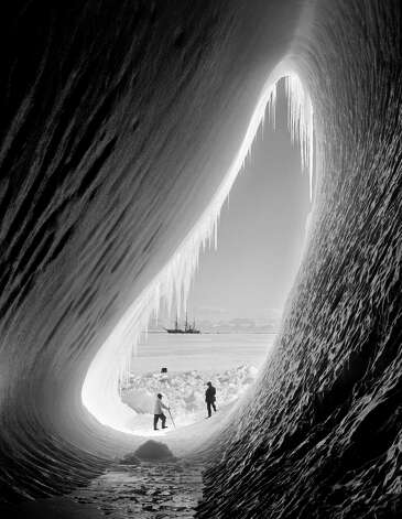 Geologist Thomas Griffith Taylor (1880 - 1963) and meteorologist Charles Wright (1887 - 1975) in the entrance to an ice grotto during Captain Robert Falcon Scott's Terra Nova Expedition to the Antarctic, 5th January 1911. The 'Terra Nova' is in the background. Photo: Scott Polar Research Institute, , H.G. Pointing/Terra Nova / 2009 Getty Images