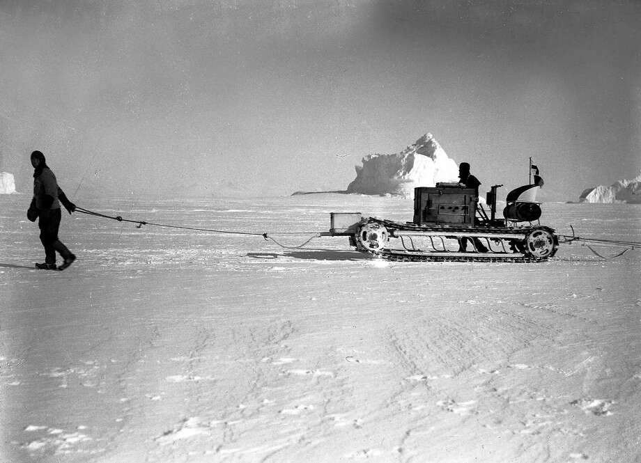 Lieutenant Evans guiding Bernard Day's motor tractor, laden with food and supplies, past the bergs on their Southern journey. Photo: Popperfoto, H.G. Pointing/Terra Nova / Popperfoto