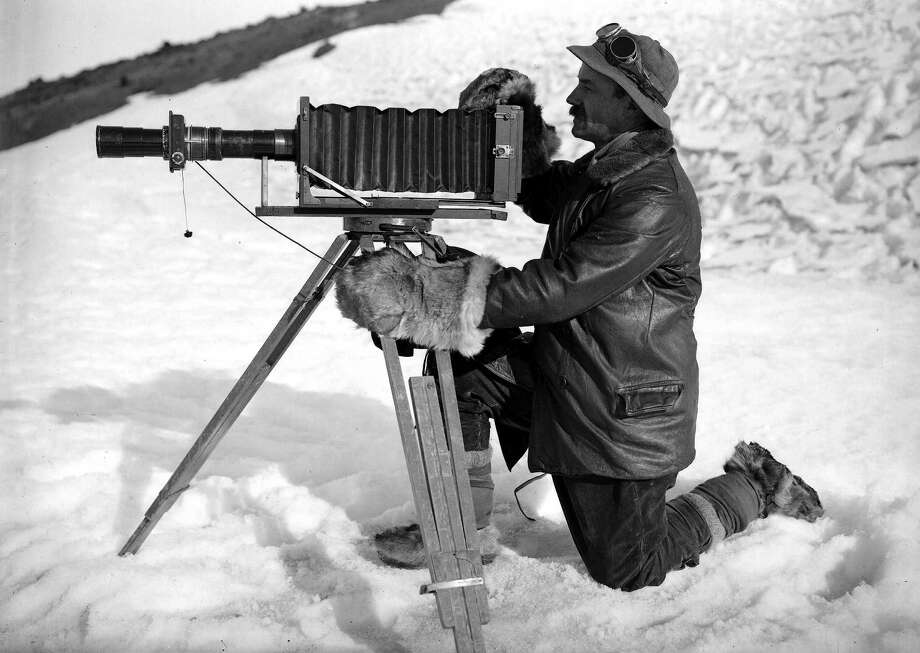 Full length portrait of photographer Herbert Ponting wearing warm clothing with his cinematograph. Photo: Popperfoto, H.G. Pointing/Terra Nova / Popperfoto