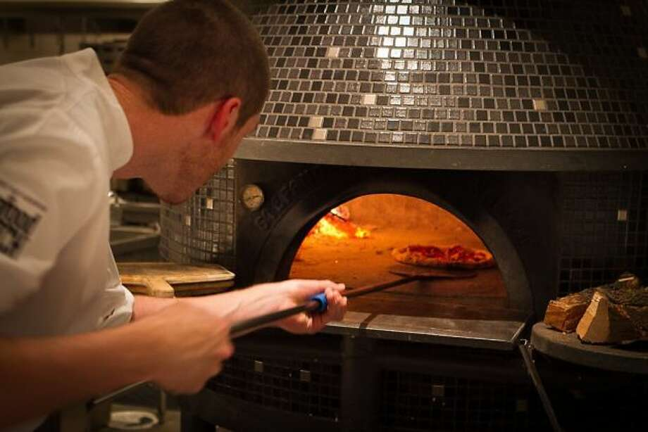 A cook puts a pizza in the oven