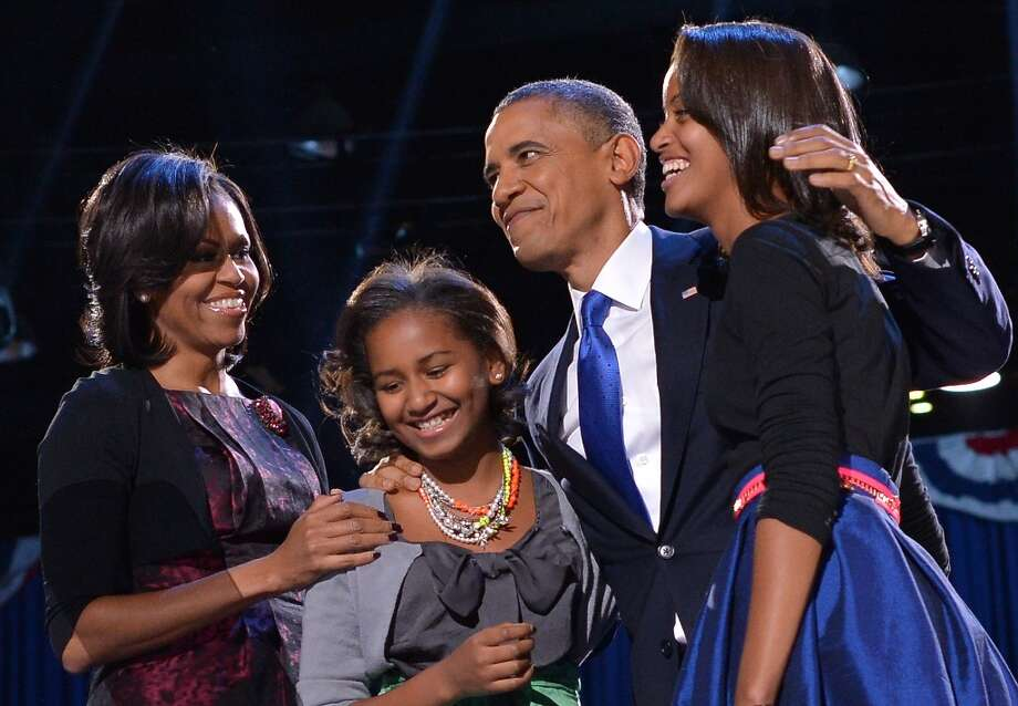 President Barack Obama accompanied by (from L-R ) First Lady Michelle and daughters Sasha and Malia appears on stage on election night November 6, 2012 in Chicago, Illinois. President Barack Obama swept to re-election Tuesday, forging history again by transcending a slow economic recovery and the high unemployment which haunted his first term to beat Republican Mitt Romney. Photo: JEWEL SAMAD, AFP/Getty Images / AFP