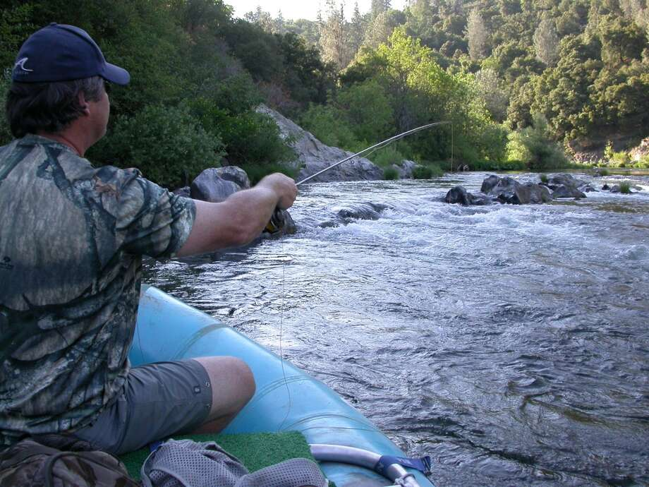 Paul Evans casts for trout on Upper Sacramento River on fishing/rafting trip with guide Jack Trout . . .