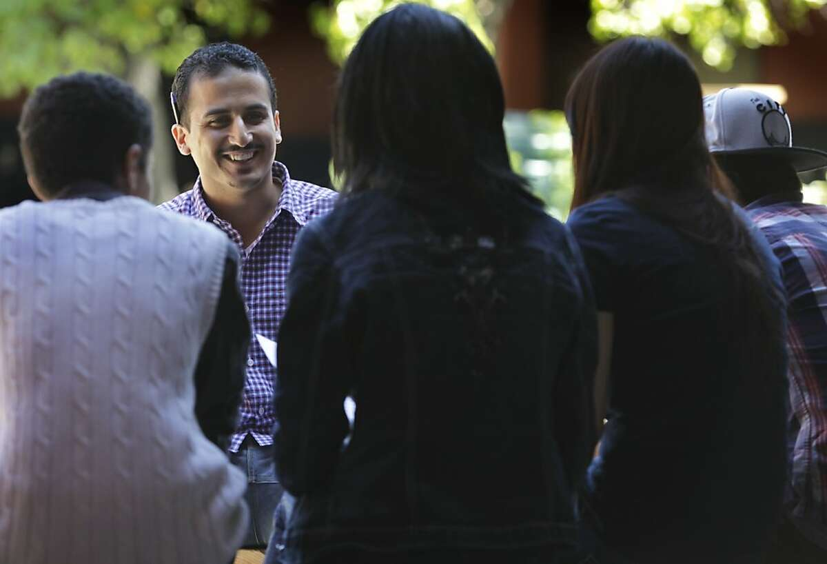 Muhmod Ahmad mentors students Yasser Alwan (left), Tati Longuele, Candice Li and Sebastian Benitez who all wrote essays on immigrating to America in the aftermath of the Boston Marathon bombings, at the International High School in Oakland, Calif. on Tuesday, April 23, 2013.
