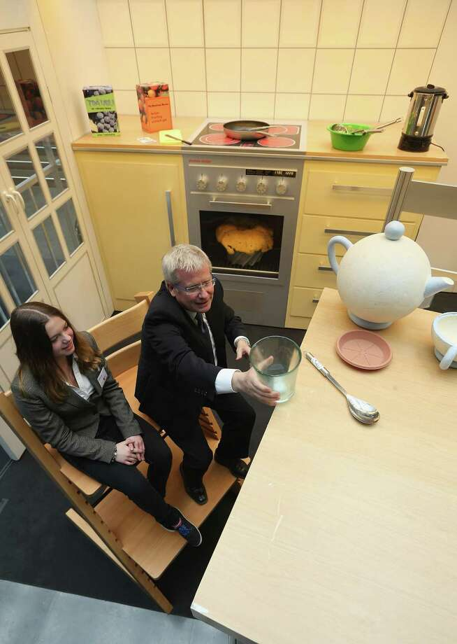 "Bundestag member and Social Democrat Fritz Rudolf Koerper and young visitor Michaela Stein explore a larger-than-life kitchen in the ""How Children See The World"" exhibit in Paul-Loebe-Haus at the Bundestag. Photo: Sean Gallup, Getty Images / 2013 Getty Images"