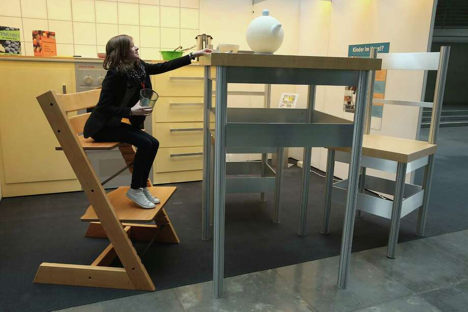 "A young woman explores a larger-than-life kitchen in the ""How Children See The World"" exhibit in Paul-Loebe-Haus at the Bundestag on April 25, 2013 in Berlin, Germany. The exhibit, which features an over-scaled kitchen complete with a breakfast table, chairs, a kitchen counter, oven and frying pan, marks the 25th anniversary of the Bundestag's Children's Commission and highlights the challenges and the dangers children face in everyday life. Photo: Sean Gallup, Getty Images / 2013 Getty Images"