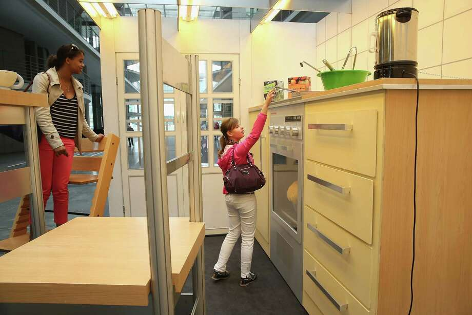 """Two young women explore a larger-than-life kitchen in the """"How Children See The World"""" exhibit in Paul-Loebe-Haus at the Bundestag on April 25, 2013 in Berlin. Photo: Sean Gallup, Getty Images / 2013 Getty Images"""
