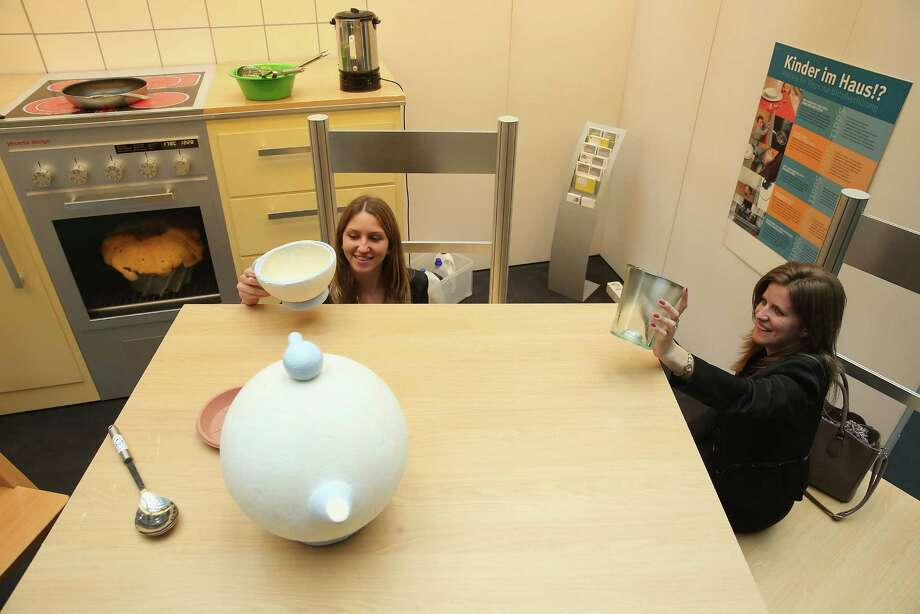 "Two young women, both interns at the Bundestag, explore a larger-than-life kitchen in the ""How Children see The Wold"" exhibit in Paul-Loebe-Haus at the Bundestag. Photo: Sean Gallup, Getty Images / 2013 Getty Images"