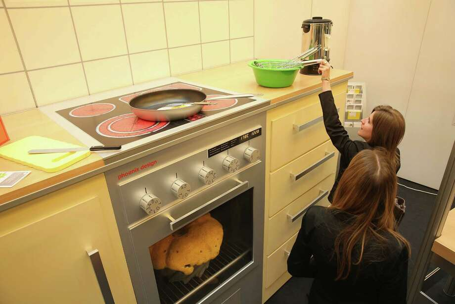 """Two young women, both interns at the Bundestag, explore a larger-than-life kitchen in the """"How Children see The Wold"""" exhibit in Paul-Loebe-Haus at the Bundestag. Photo: Sean Gallup, Getty Images / 2013 Getty Images"""