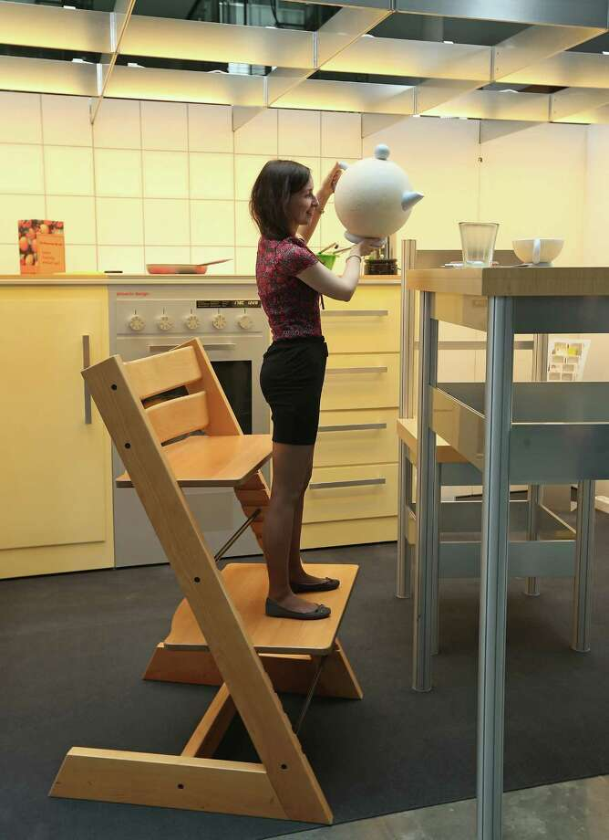 "Tatyana Sukhareva, and intern at the Bundestag, stands on a child's bigger-than-life highchair as she pretends to take coffee while exploring the ""How Children see The Wold"" exhibit in Paul-Loebe-Haus at the Bundestag. Photo: Sean Gallup, Getty Images / 2013 Getty Images"