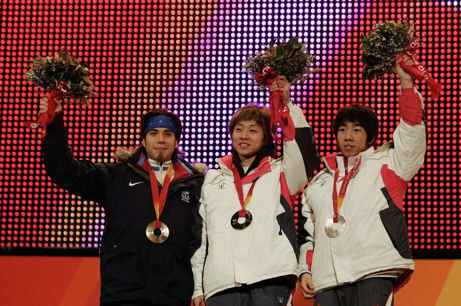 Hyun-Soo Ahn of Korea receives the gold medal Ho-Suk Lee of Korea (right) receives the silver medal Apolo Anton Ohno receives the bronze medal in the men's 1000m Short Track speed skating during the Medals Ceremony on Day 9 of the Turin 2006 Winter Olympic Games on Feb. 19, 2006 at the Medals Plaza in Turin, Italy. Photo: Stephen Munday, Getty Images / 2006 Getty Images