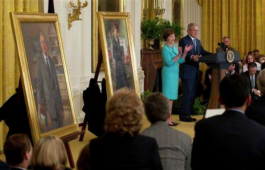 Former President George W. Bush and former first lady Laura Bush stand on stage in the East Room of the White House in Washington, Thursday, May 31, 2012, during the unveiling ceremony of their portraits. (AP Photo/Carolyn Kaster) Photo: Carolyn Kaster, AP / AP