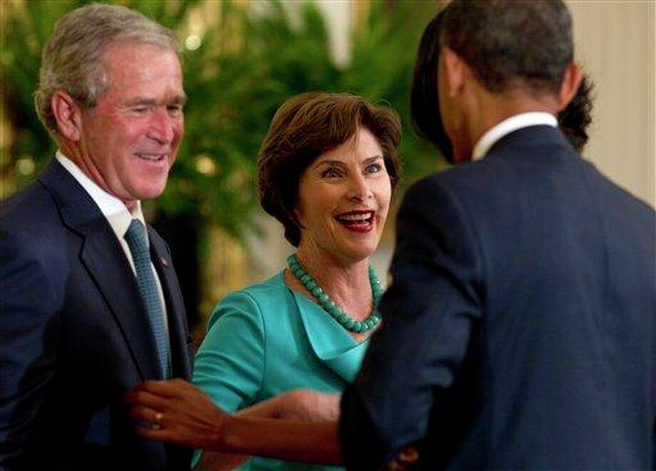 President Barack Obama greets former President George W. Bush and former first lady Laura Bush in the East Room of the White House in Washington, Thursday, May 31, 2012, during ceremony to unveil the Bush portraits. (AP Photo/Carolyn Kaster) Photo: Carolyn Kaster, AP / AP