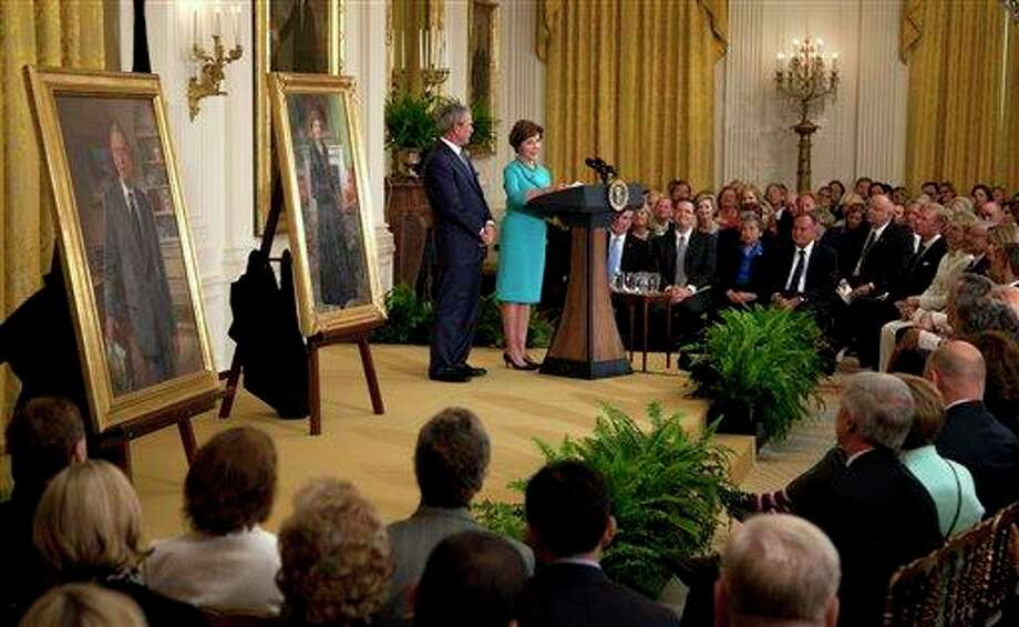 Former President George W. Bush and former first lady Laura Bush stand together on stage during a ceremony to unveil their portraits in the East Room of the White House in Washington, Thursday, May 31,2012. (AP Photo/Carolyn Kaster) Photo: Carolyn Kaster, AP / AP