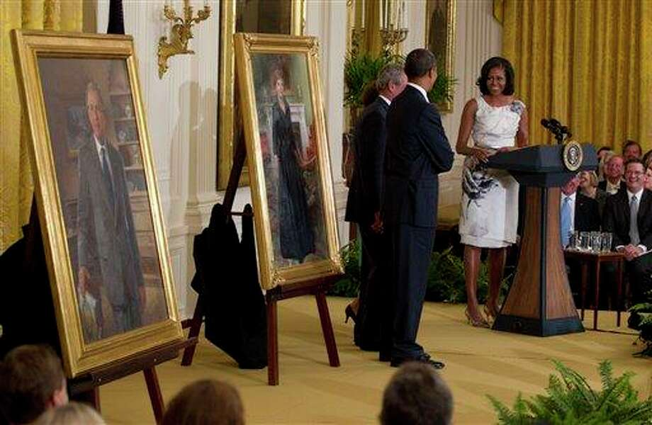First lady Michelle Obama speaks during a during a ceremony to unveil the portraits of former President George W. Bush and former first lady Laura Bush, both standing left with President Barack Obama in the East Room of the White House in Washington, Thursday, May 31,2012. (AP Photo/Carolyn Kaster) Photo: Carolyn Kaster, AP / AP