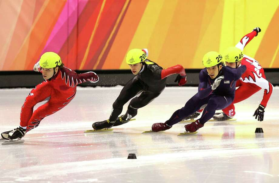 Apolo Anton Ohno of the United States looks to take the lead against Francois-Louis Tremblay of Canada (Front) and Wim de Deyne of Belgium on the final day of the men's 500 meter quarterfinals of Short Track Speed Skating on Day 15 of the Turin 2006 Winter Olympic Games on Feb. 25, 2006 at Palavela in Turin, Italy. Photo: Al Bello, Getty Images / 2006 Getty Images